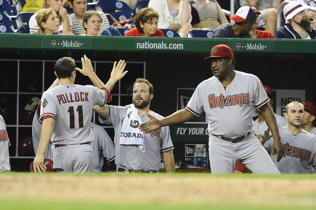 Jun 27, 2013; Washington, DC, USA; Arizona Diamondbacks center fielder A.J. Pollock (11) is congratulated by coach Don Baylor (right) after scoring a run during the eleventh inning against the Washington Nationals at Nationals Park.  Mandatory Credit: Brad Mills-USA TODAY Sports