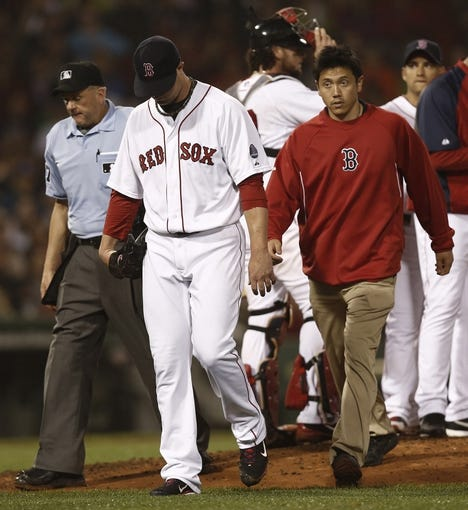 Jun 27, 2013; Boston, MA, USA;  Boston Red Sox starting pitcher Jon Lester leaves the mound with a trainer after hurting himself throwing a pitch against the Toronto Blue Jays during the eighth inning at Fenway Park. Mandatory Credit: Winslow Townson-USA TODAY Sports