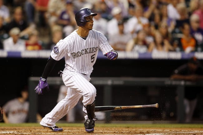 Jun 28, 2013; Denver, CO, USA; Colorado Rockies left fielder Carlos Gonzalez (5) hits an RBI double during the first inning against the San Francisco Giants at Coors Field. Mandatory Credit: Chris Humphreys-USA TODAY Sports