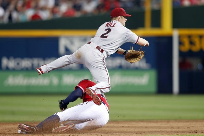 Jun 28, 2013; Atlanta, GA, USA; Arizona Diamondbacks second baseman Aaron Hill (2) turns a double play against the Atlanta Braves in the third inning at Turner Field. Mandatory Credit: Brett Davis-USA TODAY Sports