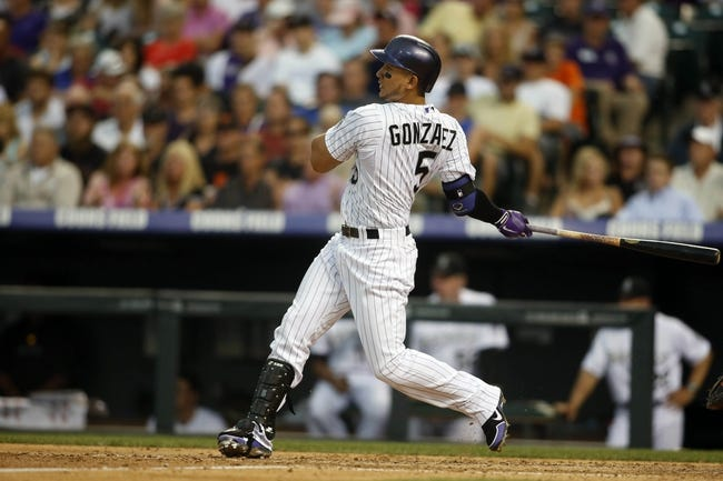 Jun 28, 2013; Denver, CO, USA; Colorado Rockies left fielder Carlos Gonzalez (5) hits a single during the fourth inning against the San Francisco Giants at Coors Field. Mandatory Credit: Chris Humphreys-USA TODAY Sports