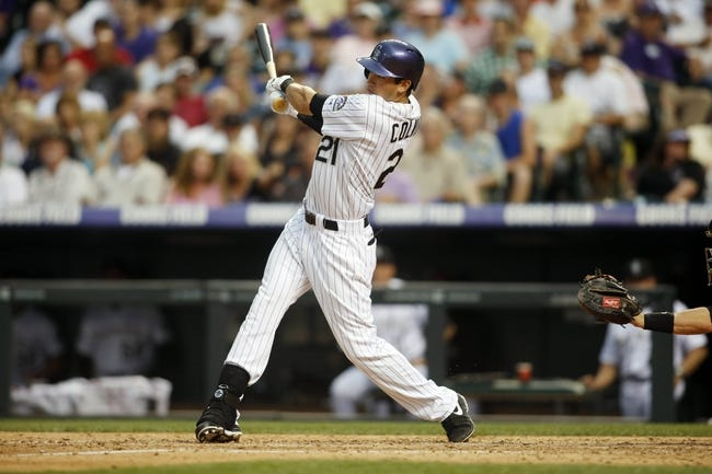 Jun 28, 2013; Denver, CO, USA; Colorado Rockies center fielder Tyler Colvin (21) hits a single during the fifth inning against the San Francisco Giants at Coors Field. Mandatory Credit: Chris Humphreys-USA TODAY Sports