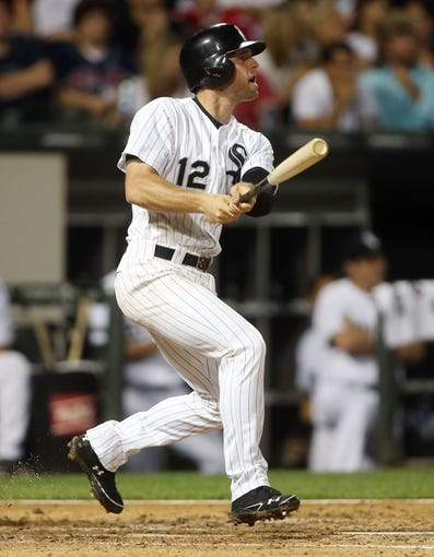 Jun 28, 2013; Chicago, IL, USA; Chicago White Sox third baseman Conor Gillaspie (12) drives in a run with a sacrifice fly against the Cleveland Indians during the first inning in the second game of a baseball doubleheader at US Cellular Field. Mandatory Credit: Jerry Lai-USA TODAY Sports