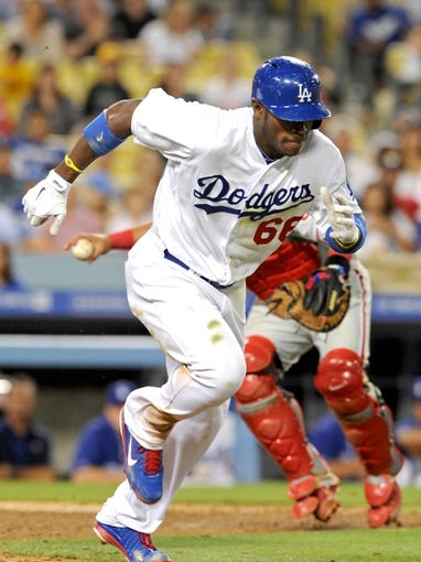 Jun 28, 2013; Los Angeles, CA, USA;  Philadelphia Phillies catcher Carlos Ruiz (51) throws out Los Angeles Dodgers right fielder Yasiel Puig (66) at first base in the eighth inning at Dodger Stadium. Phillies won 16-1. Mandatory Credit: Jayne Kamin-Oncea-USA TODAY Sports