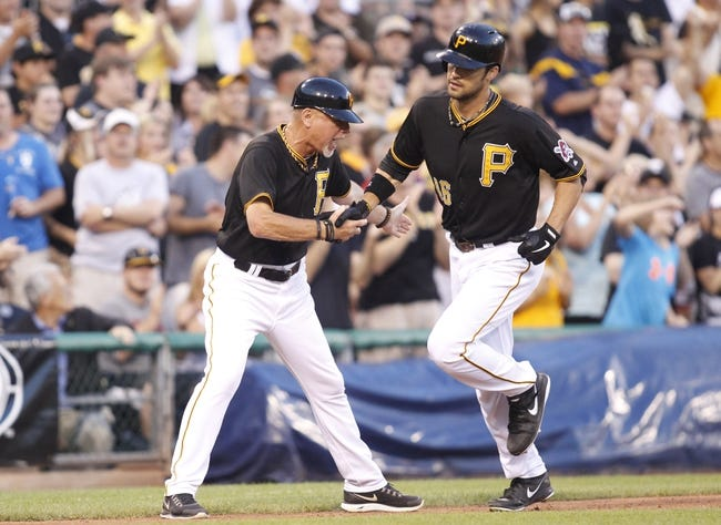 Jun 29, 2013; Pittsburgh, PA, USA; Pittsburgh Pirates third base coach Rick Sofield (left) greets first baseman Garrett Jones (46) as Jones rounds the bases after hitting a solo home run against the Milwaukee Brewers during the fourth inning at PNC Park. The Pittsburgh Pirates won 2-1. Mandatory Credit: Charles LeClaire-USA TODAY Sports