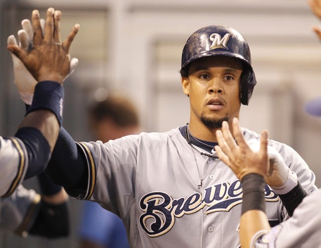 Jun 29, 2013; Pittsburgh, PA, USA; Milwaukee Brewers center fielder Carlos Gomez (27) is greeted in the dugout after scoring a run against the Pittsburgh Pirates during the sixth inning at PNC Park. The Pittsburgh Pirates won 2-1. Mandatory Credit: Charles LeClaire-USA TODAY Sports