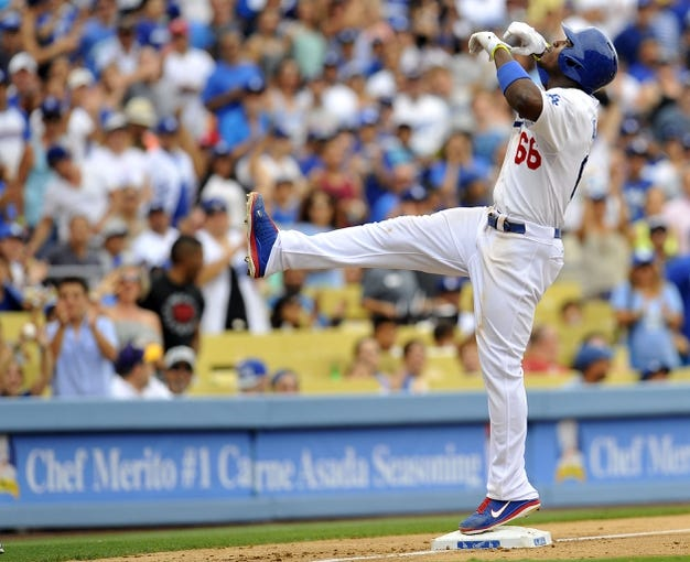 June 30, 2013; Los Angeles, CA, USA; Los Angeles Dodgers right fielder Yasiel Puig (66) reacts after reaching third after hitting a triple during the fifth inning against the Philadelphia Phillies at Dodger Stadium. Mandatory Credit: Gary A. Vasquez-USA TODAY Sports
