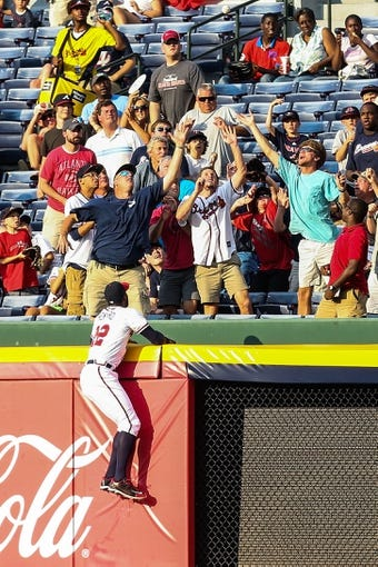 Jul 2, 2013; Atlanta, GA, USA; Atlanta Braves right fielder Jason Heyward (22) climbs the wall in an attempt to catch a home run in the first inning against the Miami Marlins at Turner Field. Mandatory Credit: Daniel Shirey-USA TODAY Sports