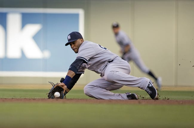 Jul 2, 2013; Minneapolis, MN, USA; New York Yankees second baseman Robinson Cano (24) dives for a ground ball in the first inning against the Minnesota Twins at Target Field. Mandatory Credit: Jesse Johnson-USA TODAY Sports