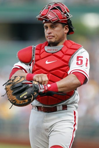 Jul 2, 2013; Pittsburgh, PA, USA; Philadelphia Phillies catcher Carlos Ruiz (51) adjusts his equipment before the inning against the Pittsburgh Pirates during the second inning at PNC Park. The Philadelphia Phillies won 3-1. Mandatory Credit: Charles LeClaire-USA TODAY Sports