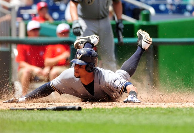Jul 4, 2013; Washington, DC, USA; Milwaukee Brewers outfielder Carlos Gomez (27) slides in to home plate to score a run in the sixth inning against the Washington Nationals at Nationals Park. Mandatory Credit: Evan Habeeb-USA TODAY Sports