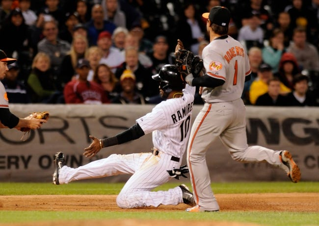 Jul 2, 2013; Chicago, IL, USA; Chicago White Sox shortstop Alexei Ramirez (10) tries to slide into third base underneath Baltimore Orioles third baseman Manny Machado (13) during the seventh inning at U.S. Cellular Field. Mandatory Credit: Reid Compton-USA TODAY Sports