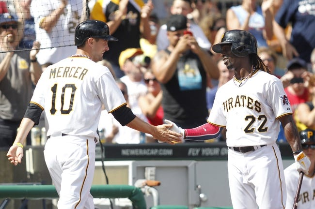 Jul 4, 2013; Pittsburgh, PA, USA; Pittsburgh Pirates shortstop Jordy Mercer (10) is greeted after crossing home plate to score a run by center fielder Andrew McCutchen (22) during the eighth inning against the Philadelphia Phillies at PNC Park. The Philadelphia Phillies won 6-4. Mandatory Credit: Charles LeClaire-USA TODAY Sports