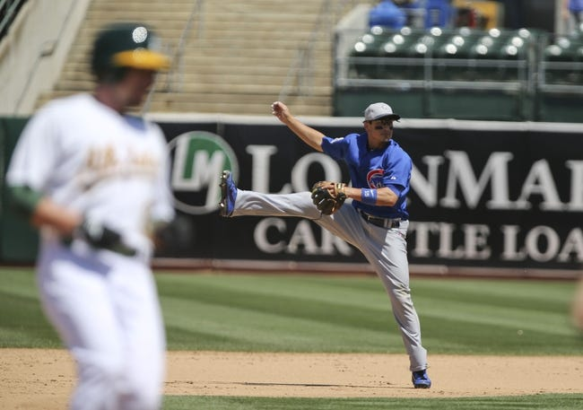 Jul 4, 2013; Oakland, CA, USA; Chicago Cubs second baseman Darwin Barney (15) leaps for the ball as Oakland Athletics shortstop Jed Lowrie (8) advances to third base during the sixth inning at O.co Coliseum. Mandatory Credit: Kelley L Cox-USA TODAY Sports