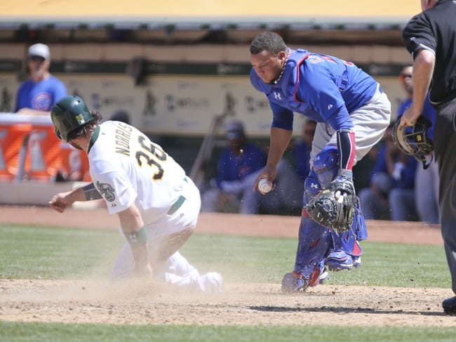 Jul 4, 2013; Oakland, CA, USA; Oakland Athletics catcher Derek Norris (36) scores a run on a passed ball against Chicago Cubs catcher Welington Castillo (53) during the seventh inning at O.co Coliseum. Mandatory Credit: Kelley L Cox-USA TODAY Sports