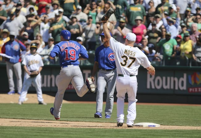 Jul 4, 2013; Oakland, CA, USA; Chicago Cubs right fielder Nate Schierholtz (19) reaches first base against Oakland Athletics first baseman Brandon Moss (37) on a throwing error by shortstop Jed Lowrie (not pictured) during the ninth inning at O.co Coliseum. The Oakland Athletics defeated the Chicago Cubs 1-0. Mandatory Credit: Kelley L Cox-USA TODAY Sports