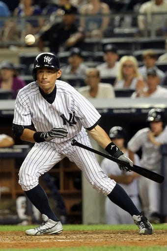 Jul 5, 2013; Bronx, NY, USA; New York Yankees right fielder Ichiro Suzuki (31) drops down a sacrifice bunt against the Baltimore Orioles during the ninth inning of a game at Yankee Stadium. Mandatory Credit: Brad Penner-USA TODAY Sports