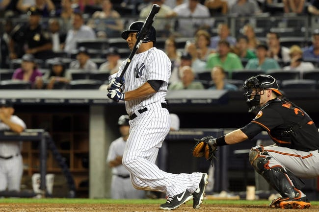 Jul 5, 2013; Bronx, NY, USA; New York Yankees left fielder Vernon Wells (12) hits a game-winning RBI single against the Baltimore Orioles during the ninth inning of a game at Yankee Stadium. Mandatory Credit: Brad Penner-USA TODAY Sports