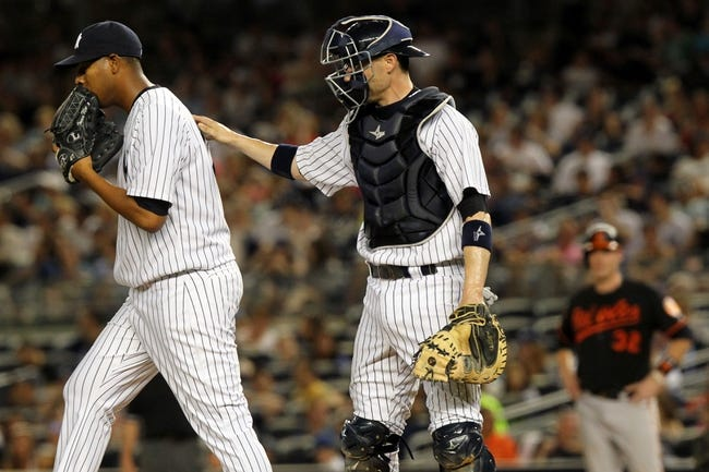 Jul 5, 2013; Bronx, NY, USA; New York Yankees catcher Chris Stewart (19) talks with starting pitcher Ivan Nova (47) after a walk to Baltimore Orioles catcher Matt Wieters (32) during the seventh inning of a game at Yankee Stadium. Mandatory Credit: Brad Penner-USA TODAY Sports