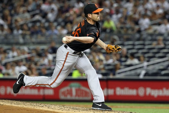Jul 5, 2013; Bronx, NY, USA; Baltimore Orioles relief pitcher Darren O'Day (56) pitches against the New York Yankees during the eighth inning of a game at Yankee Stadium. Mandatory Credit: Brad Penner-USA TODAY Sports