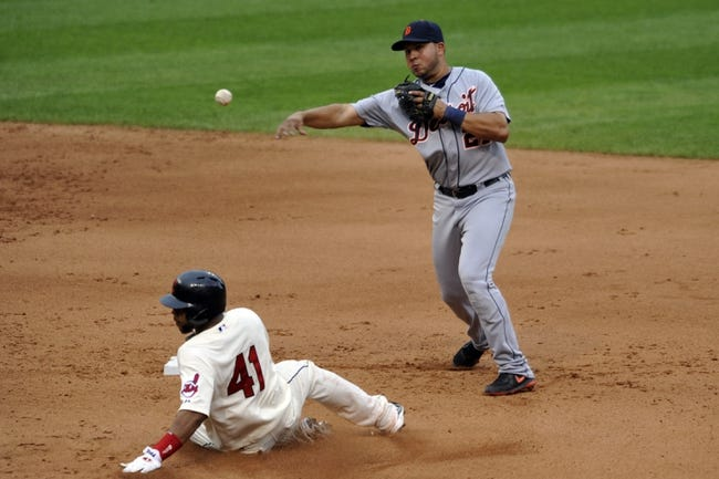 Jul 6, 2013; Cleveland, OH, USA; Detroit Tigers shortstop Jhonny Peralta (27) turns a double play over Cleveland Indians catcher Carlos Santana (41) in the seventh inning at Progressive Field. Mandatory Credit: David Richard-USA TODAY Sports