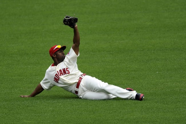 Jul 7, 2013; Cleveland, OH, USA; Cleveland Indians center fielder Michael Bourn (24) makes a catch on a ball hit by Detroit Tigers center fielder Austin Jackson (not pictured) in the first inning at Progressive Field. Mandatory Credit: David Richard-USA TODAY Sports
