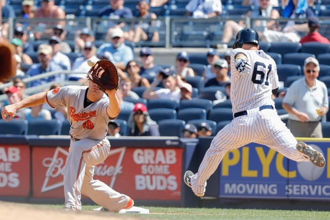 Jul 7, 2013; Bronx, NY, USA;  New York Yankees third baseman Luis Cruz (61) is out at first as Baltimore Orioles first baseman Chris Davis (19) is on the bag during the sixth inning at Yankee Stadium. Baltimore Orioles won 2-1.  Mandatory Credit: Anthony Gruppuso-USA TODAY Sports