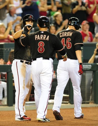 Jul 7, 2013; Phoenix, AZ, USA; Arizona Diamondbacks third baseman Eric Chavez (12) high fives center fielder Gerardo Parra (8) after Gerardo Parra (8) and Patrick Corbin (46) scored in the third inning during a game against the Colorado Rockies at Chase Field. Mandatory Credit: Jennifer Hilderbrand-USA TODAY Sports