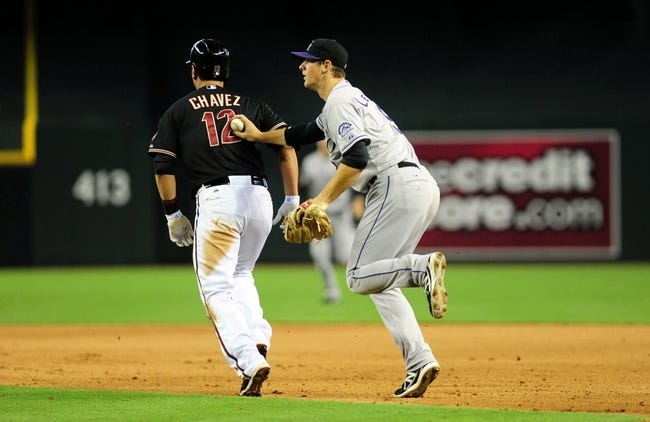Jul 7, 2013; Phoenix, AZ, USA; Arizona Diamondbacks base runner Eric Chavez (12) is caught in a pickle and is out by Colorado Rockies second baseman D.J. LeMahieu (9) during the fifth inning during a game against the Colorado Rockies at Chase Field. Mandatory Credit: Jennifer Hilderbrand-USA TODAY Sports