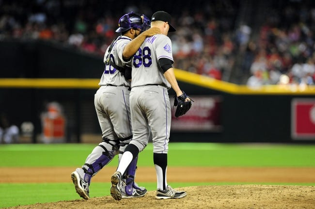 Jul 7, 2013; Phoenix, AZ, USA; Colorado Rockies pitcher Josh Outman (88) and catcher Wilin Rosario (20) talk on the mound during the sixth inning during a game against the Arizona Diamondbacks at Chase Field. Mandatory Credit: Jennifer Hilderbrand-USA TODAY Sports