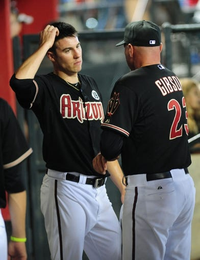 Jul 7, 2013; Phoenix, AZ, USA; Arizona Diamondbacks pitcher Patrick Corbin (left) talks with manager Kirk Gibson (right) in the eighth inning during a game against the Colorado Rockies at Chase Field. Mandatory Credit: Jennifer Hilderbrand-USA TODAY Sports