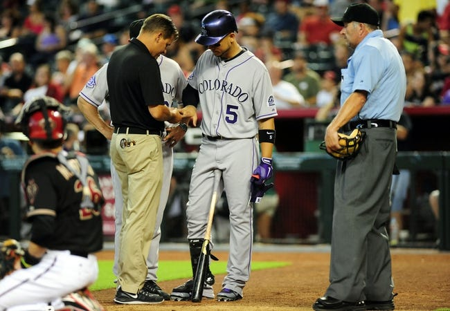 Jul 7, 2013; Phoenix, AZ, USA; Colorado Rockies batter Carlos Gonzalez (5) talks with a trainer in the ninth inning during a game against the Arizona Diamondbacks at Chase Field. Mandatory Credit: Jennifer Hilderbrand-USA TODAY Sports