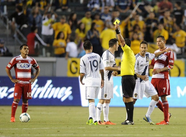 Jul 7, 2013; Carson, CA, USA; A yellow card is issued to Los Angeles Galaxy midfielder Juninho (19) by referee Ricardo Salazar during the game against the FC Dallas during the first half at the StubHub Center. Mandatory Credit: Kelvin Kuo-USA TODAY Sports