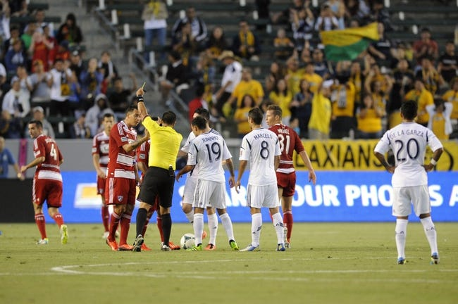 Jul 7, 2013; Carson, CA, USA; A yellow card is issued to FC Dallas midfielder David Ferreira (10) by referee Ricardo Salazar during the game against the Los Angeles Galaxy during the first half at the StubHub Center. Mandatory Credit: Kelvin Kuo-USA TODAY Sports