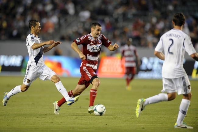 Jul 7, 2013; Carson, CA, USA; FC Dallas midfielder Andrew Jacobson (4) moves the ball down the field defended by Los Angeles Galaxy midfielder Marcelo Sarvas (8) during the first half at the StubHub Center. Mandatory Credit: Kelvin Kuo-USA TODAY Sports