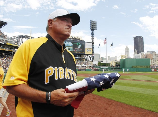 Jul 4, 2013; Pittsburgh, PA, USA; Pittsburgh Pirates manager Clint Hurdle (13) carries an American flag on the field before playing the Philadelphia Phillies at PNC Park. The Philadelphia Phillies won 6-4.Mandatory Credit: Charles LeClaire-USA TODAY Sports
