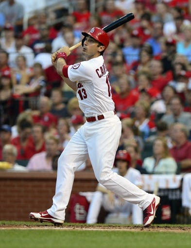 Jul 9, 2013; St. Louis, MO, USA; St. Louis Cardinals second baseman Matt Carpenter (13) hits a sacrifice fly off of Houston Astros starting pitcher Bud Norris (not pictured) during the second inning at Busch Stadium. Mandatory Credit: Jeff Curry-USA TODAY Sports