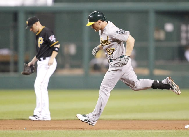 Jul 9, 2013; Pittsburgh, PA, USA; Oakland Athletics first baseman Brandon Moss (37) rounds the bases after hitting a two run home run as Pittsburgh Pirates shortstop Clint Barmes (left) reacts during the fourth inning at PNC Park. The Oakland Athletics won 2-1. Mandatory Credit: Charles LeClaire-USA TODAY Sports