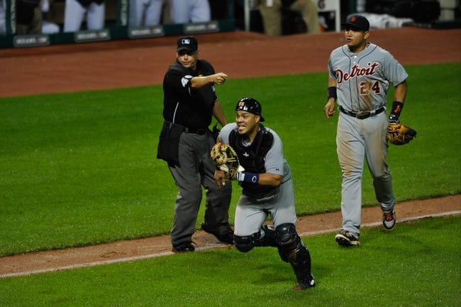 Jul 8, 2013; Cleveland, OH, USA; As home plate umpire Andy Fletcher makes the call beside Detroit Tigers third baseman Miguel Cabrera (24), catcher Brayan Pena runs at Cleveland Indians first baseman Nick Swisher (not pictured) after his foul ball down the third base line rolled back in to fair territory at Progressive Field. Swisher was tagged out near home plate and Detroit won 4-2. Mandatory Credit: David Richard-USA TODAY Sports