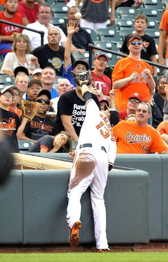 Jul 10, 2013; Baltimore, MD, USA; Baltimore Orioles third baseman Manny Machado (13) catches a pop-up by Texas Rangers third baseman Adrian Beltre (not shown) on the second inning at Oriole Park at Camden Yards. Mandatory Credit: Joy R. Absalon-USA TODAY Sports