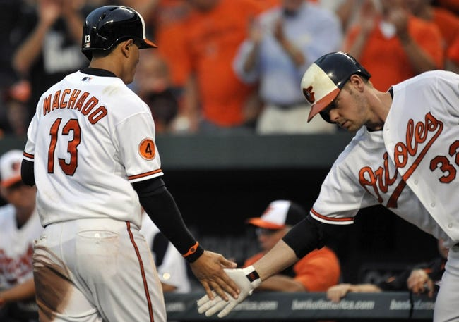 Jul 10, 2013; Baltimore, MD, USA; Baltimore Orioles third baseman Manny Machado (13) is congratulated by Matt Wieters (32) after scoring on a wild pitch by Texas Rangers pitcher Josh Lindblom (not shown) in the third inning at Oriole Park at Camden Yards. Mandatory Credit: Joy R. Absalon-USA TODAY Sports
