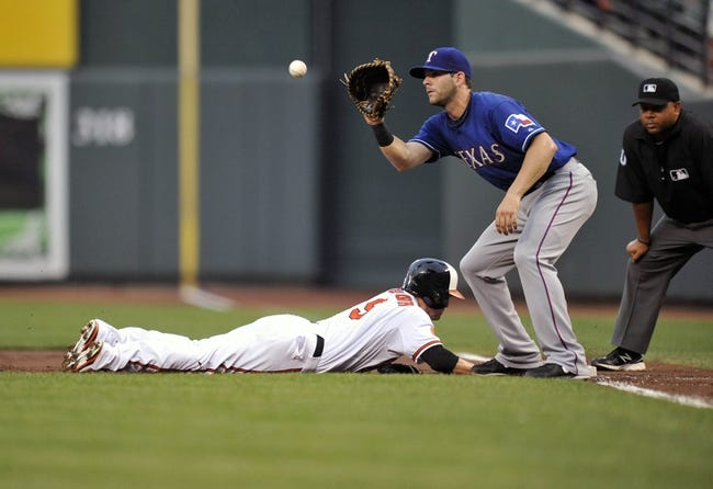 Jul 10, 2013; Baltimore, MD, USA; Baltimore Orioles left fielder Nate McLouth (9) dives back to first base safely against the tag of Texas Rangers first baseman Mitch Moreland (18) in the third inning at Oriole Park at Camden Yards. Mandatory Credit: Joy R. Absalon-USA TODAY Sports