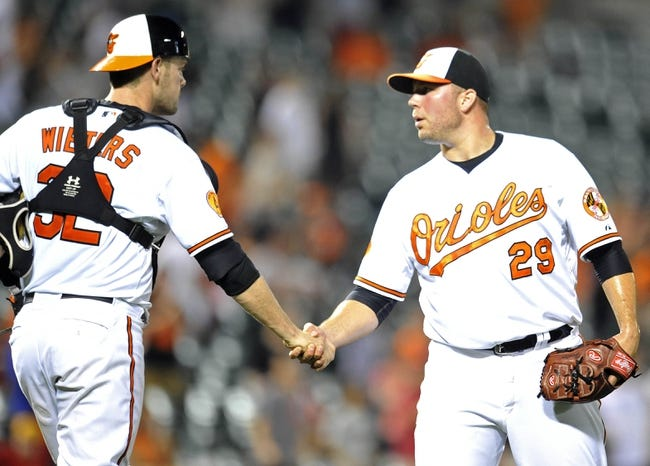 Jul 10, 2013; Baltimore, MD, USA; Baltimore Orioles catcher Matt Wieters (32) congratulates pitcher Tommy Hunter (29) after a game against the Texas Rangers at Oriole Park at Camden Yards. The Orioles defeated the Rangers 6-1. Mandatory Credit: Joy R. Absalon-USA TODAY Sports