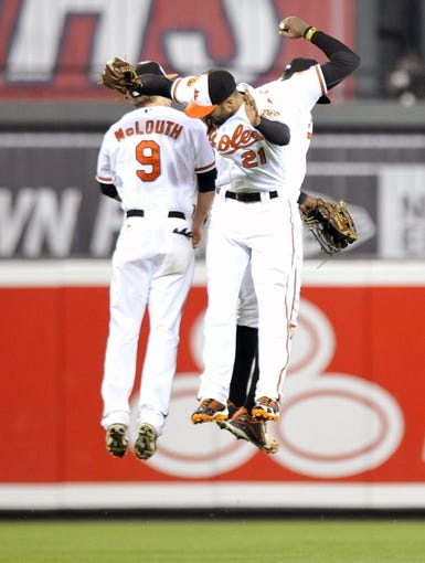 Jul 10, 2013; Baltimore, MD, USA; Baltimore Orioles outfielders Nate McLouth (left) Nick Markakis (right) and Adam Jones (back) celebrate after a game against the Texas Rangers at Oriole Park at Camden Yards. The Orioles defeated the Rangers 6-1. Mandatory Credit: Joy R. Absalon-USA TODAY Sports