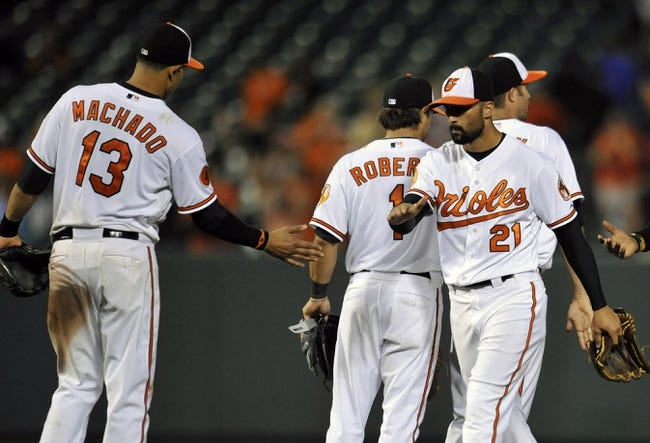 Jul 10, 2013; Baltimore, MD, USA; Baltimore Orioles teammates Manny Machado (13) and Nick Markakis (21) celebrate after a game against the Texas Rangers at Oriole Park at Camden Yards. The Orioles defeated the Rangers 6-1. Mandatory Credit: Joy R. Absalon-USA TODAY Sports