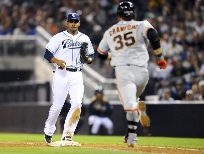 Jul 11, 2013; San Diego, CA, USA; San Diego Padres first baseman Jesus Guzman (15) makes a play at first base ahead of San Francisco Giants shortstop Brandon Crawford (35) during the eighth inning at Petco Park. Mandatory Credit: Christopher Hanewinckel-USA TODAY Sports