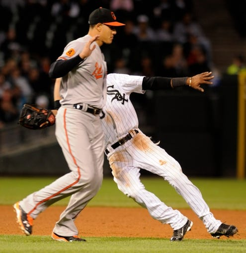 Jul 2, 2013; Chicago, IL, USA; Chicago White Sox shortstop Alexei Ramirez (10) is chased down by Baltimore Orioles third baseman Manny Machado (13) during the seventh inning at U.S. Cellular Field. Mandatory Credit: Reid Compton-USA TODAY Sports