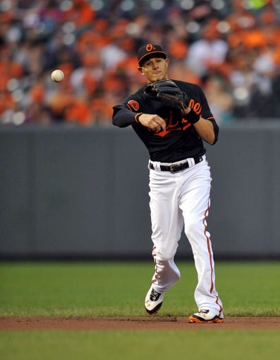 Jul 12, 2013; Baltimore, MD, USA; Baltimore Orioles third baseman Manny Machado (13) throws over to first base to get out Toronto Blue Jays designated hitter Adam Lind (not shown) in the second inning at Oriole Park at Camden Yards. Mandatory Credit: Joy R. Absalon-USA TODAY Sports