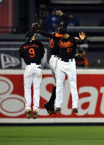 Jul 12, 2013; Baltimore, MD, USA; Baltimore Orioles outfielders Nate McLouth (left, Nick Markakis (right) and Adam Jones (back) celebrate after a game against the Toronto Blue Jays at Oriole Park at Camden Yards. The Orioles defeated the Blue Jays 8-5. Mandatory Credit: Joy R. Absalon-USA TODAY Sports