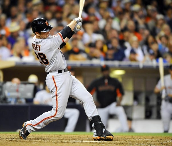 Jul 12, 2013; San Diego, CA, USA; San Francisco Giants catcher Buster Posey (28) hits home two runs during the sixth inning against the San Diego Padres at Petco Park. Mandatory Credit: Christopher Hanewinckel-USA TODAY Sports